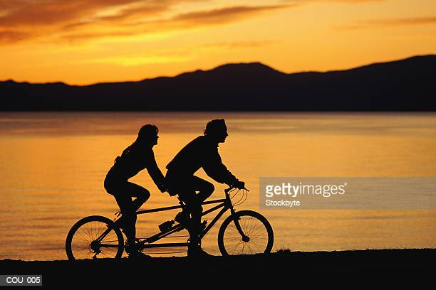 Silhouette of two people on bike
