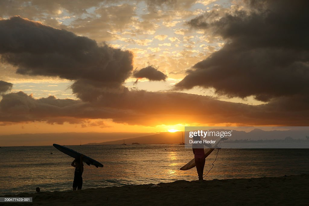 Silhouette of two women carrying surfboards at beach, sunset : Stock Photo