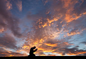 A man prays earnestly against a dramatic sunset. Themes include salvation, prayer, meditation, christianity, single, bowing, kneeling, reverence, palms open, religious, spirituality, and hope. Man is