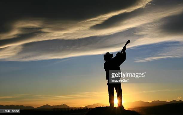 Silhouette of Western Country Music Guitar Player at Sunset