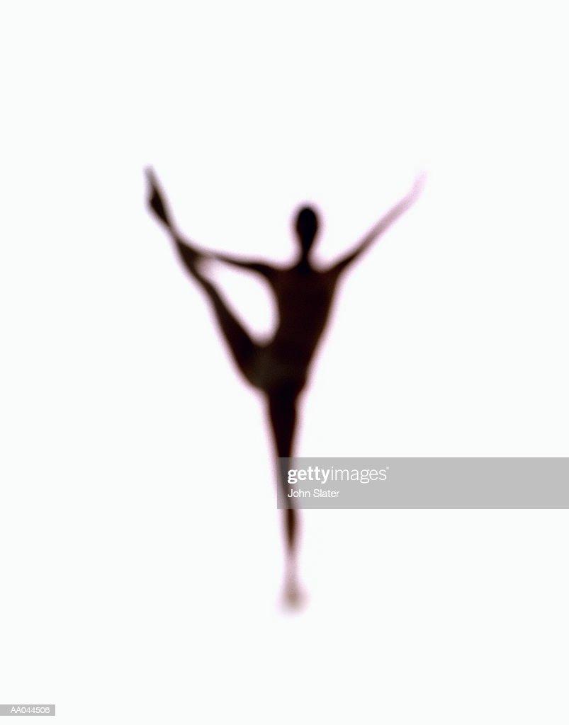 Silhouette of woman balancing on one leg : Stock Photo