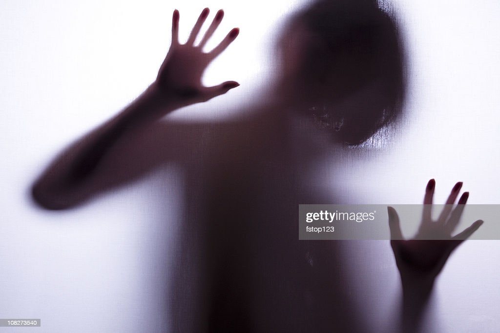 Silhouette of a Woman behind screen with arms raised : Stock Photo
