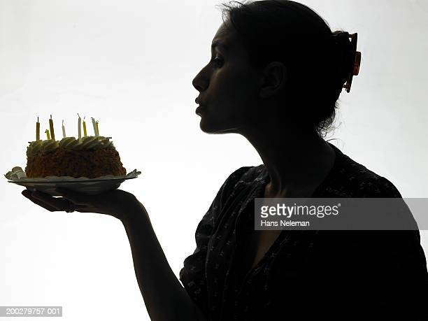 Silhouette of woman blowing out candles on cake, side view, close-up