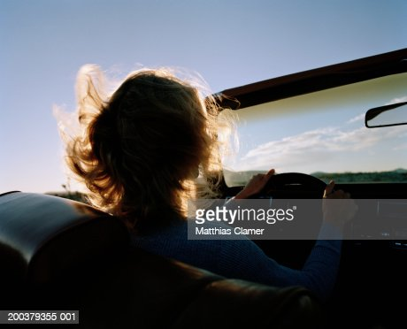 Silhouette of woman driving convertible, rear view, close-up : Stock Photo