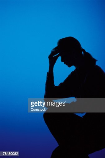 Silhouette of woman holding her head : Stock Photo