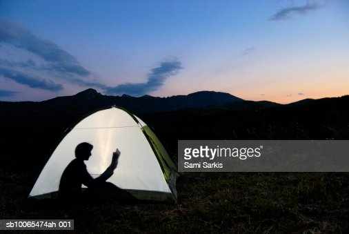 Silhouette of woman in illuminated tent, reading book : Stock Photo