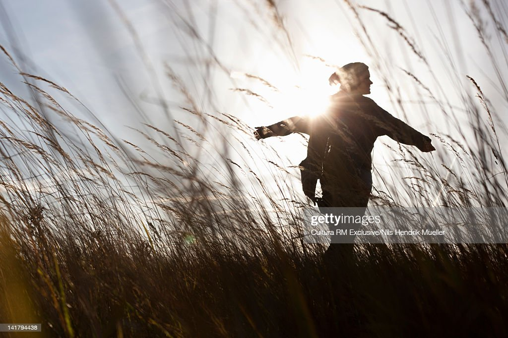 Silhouette of woman in wheatfield : Stock Photo