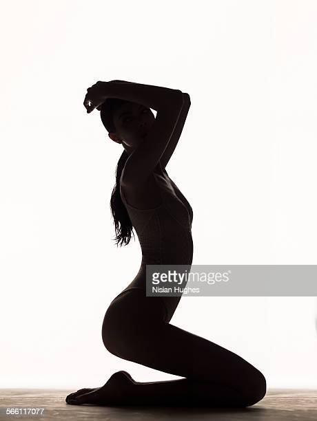 silhouette of woman kneeling in studio
