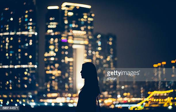Silhouette of woman looking away to cityscape