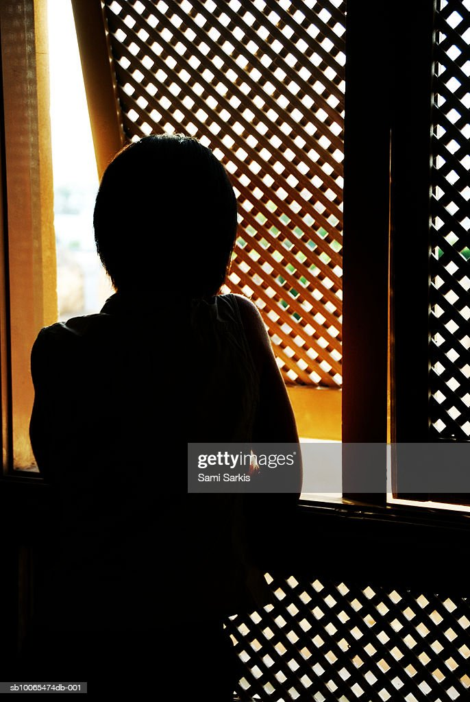 Silhouette of woman looking outside from Moucharabieh window