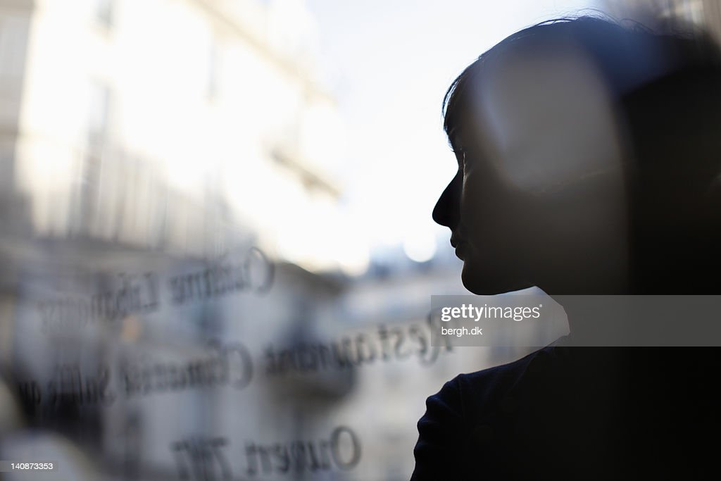 Silhouette of woman reflected in window : Stock Photo