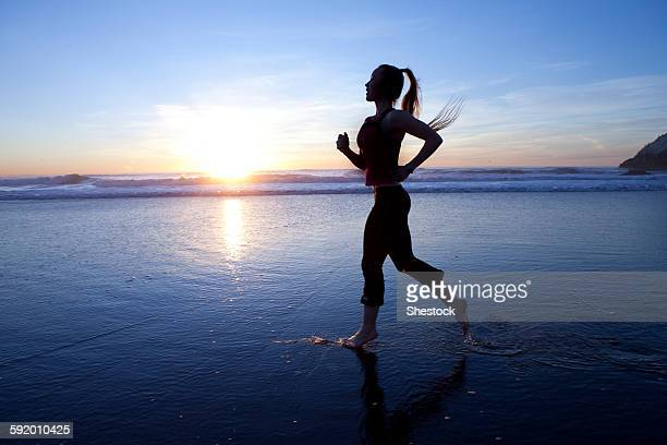 Silhouette of woman running on beach at sunrise