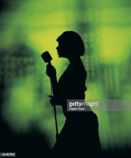 Silhouette of woman singing into microphone