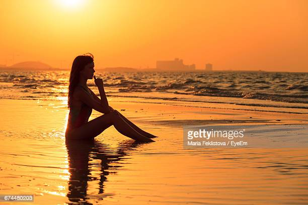 Silhouette Of Woman Sitting On The Beach At Sunset