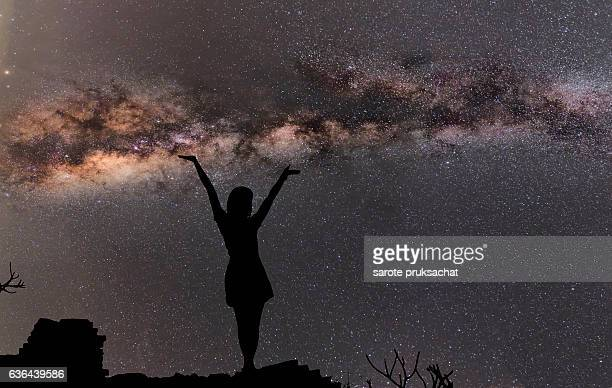 Silhouette of woman standing next to the milky way and pointing on a bright star.