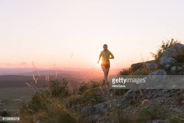 Silhouette of woman trail running on rocky terrain during sunset