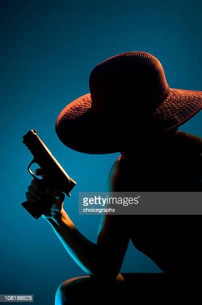 Silhouette di donna con cappello e con Pistola