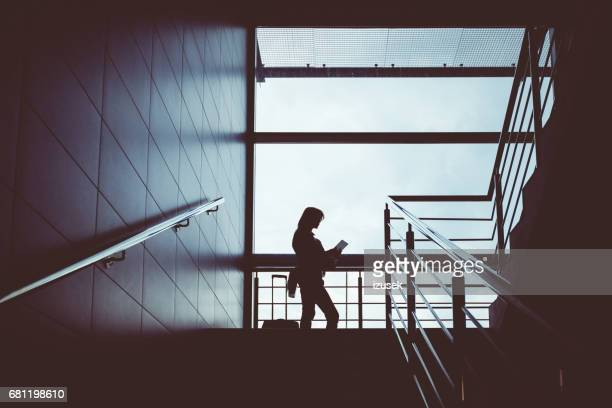Silhouette of woman with digital tablet in airport