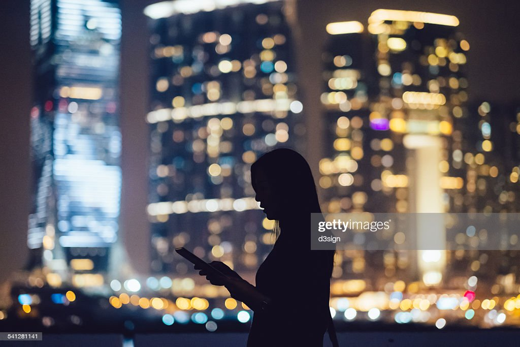 Silhouette of woman with digital tablet in city : Stock Photo
