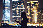 Silhouette of woman with digital tablet in city
