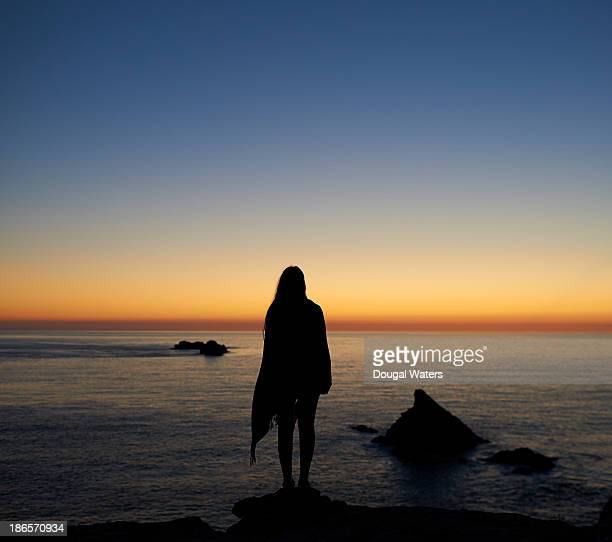 Silhouette of woman wrapped in shawl at sunset.
