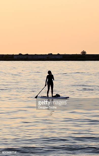 Silhouette of women paddleboarding on the calm water