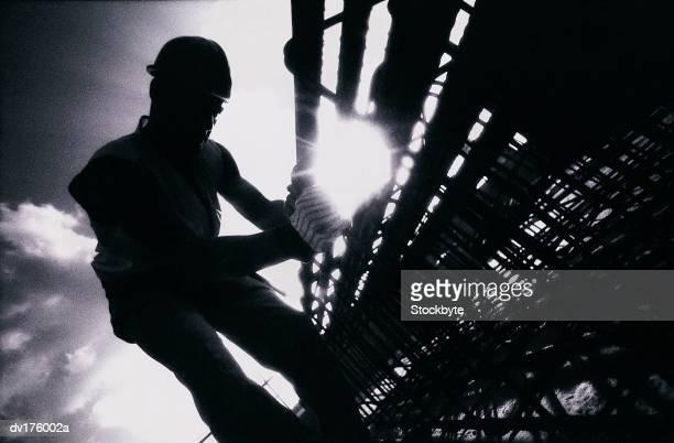 Silhouette of worker on scaffolding