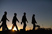 Silhouette of workers at oil refinery