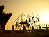 Silhouette of workers building scaffolding, low angle view