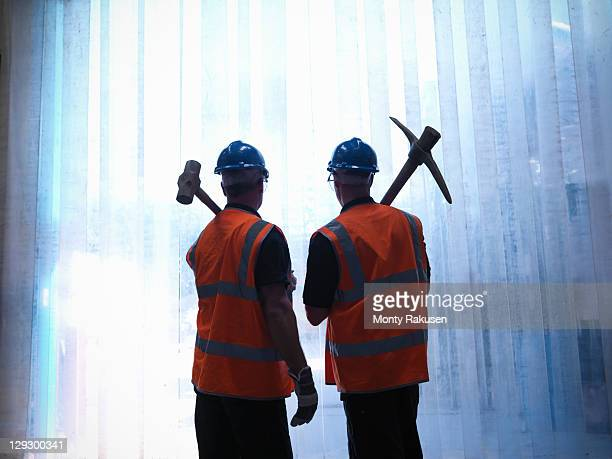Silhouette of workers holding a hammer and a pickaxe over shoulders
