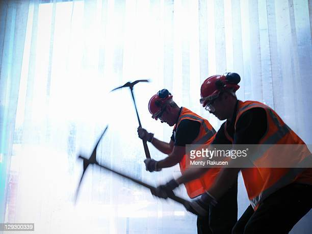 Silhouette of workers swinging pickaxes
