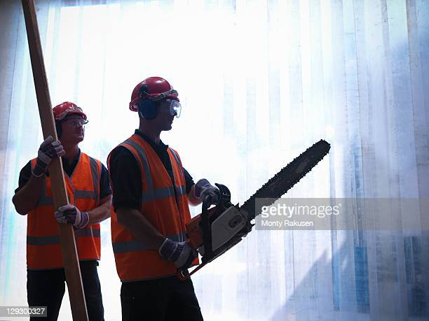 Silhouette of workers with a plank of wood and a chainsaw