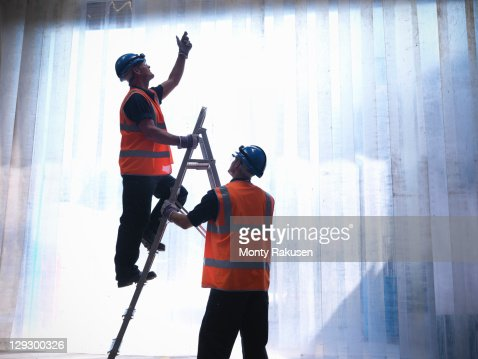 Silhouette of workers with a step ladder
