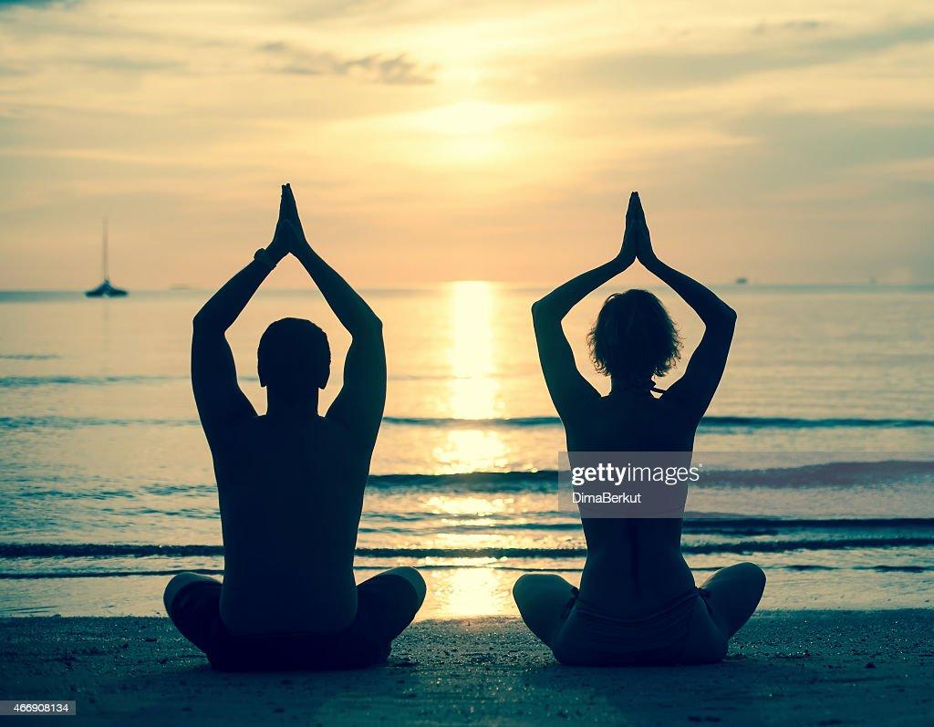 Silueta De Pareja Joven Practicar Yoga En La Playa Del Mar