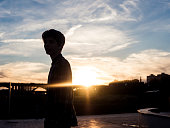 silhouette of young man standing in the city street and the sunset is behind him