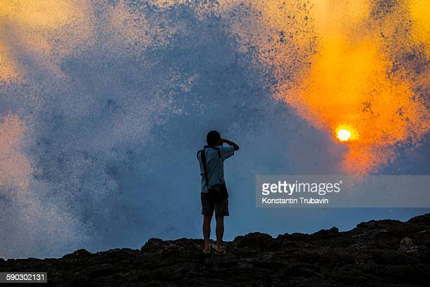 Silhouette of Young Photographer at Ocean Coast at sunset time.