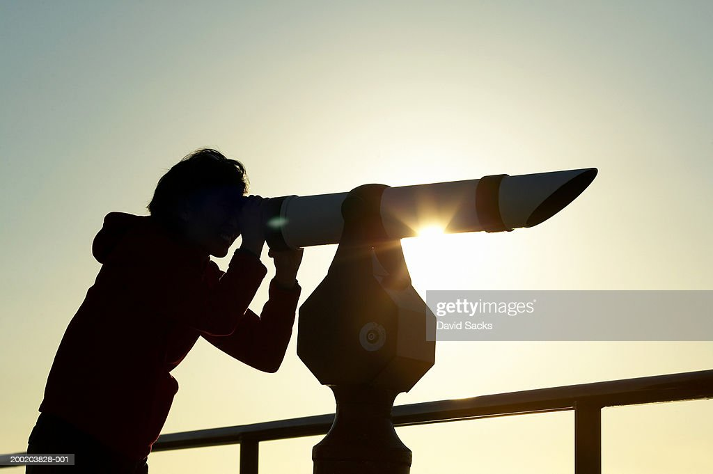 Silhouette of young woman looking through telescope : Stock Photo