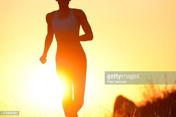 Silhouette of young woman running at sunset