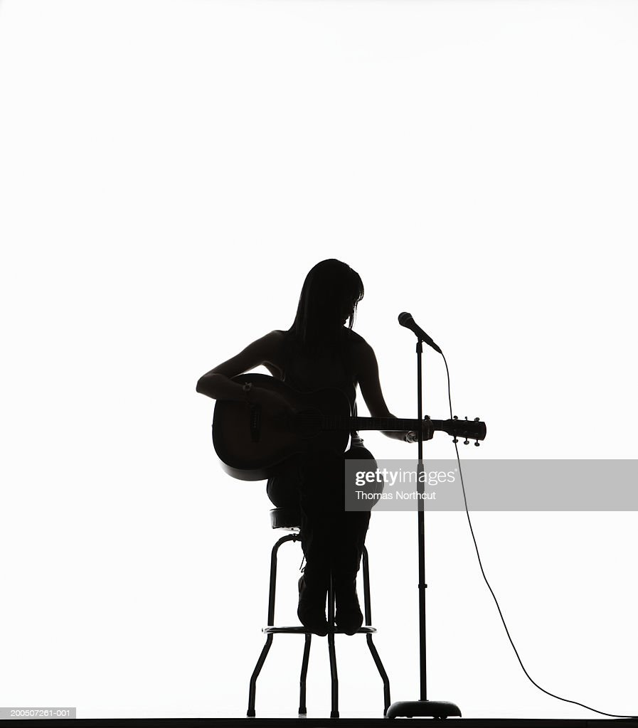 Silhouette Of Young Woman Sitting On Stool Playing ...