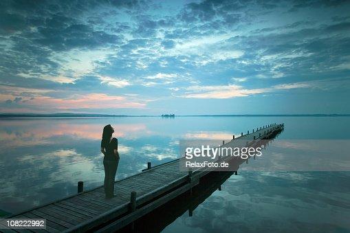 Silhouette der jungen Frau steht am See Steg im Sonnenuntergang