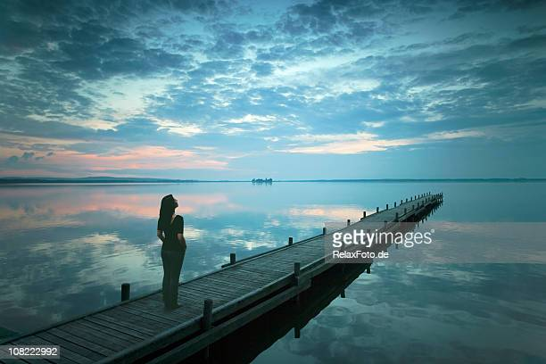 Silhouette of Young Woman Standing On Lakeside Jetty at Dusk