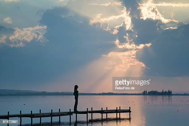 Silhouette of young woman standing on lakeside jetty in sunbeam