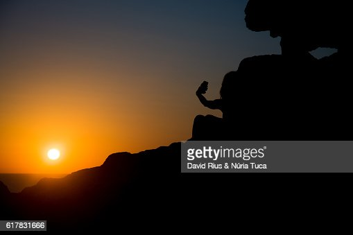 Silhouette of young woman taking a photo : ストックフォト