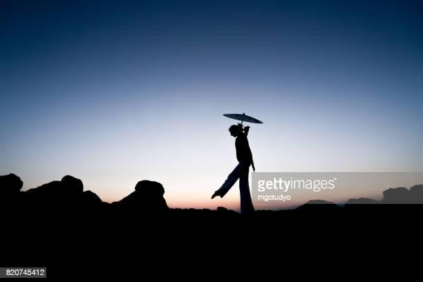 Silhouette der jungen Frau zu Fuß auf den Felsen mit massieren Regenschirm
