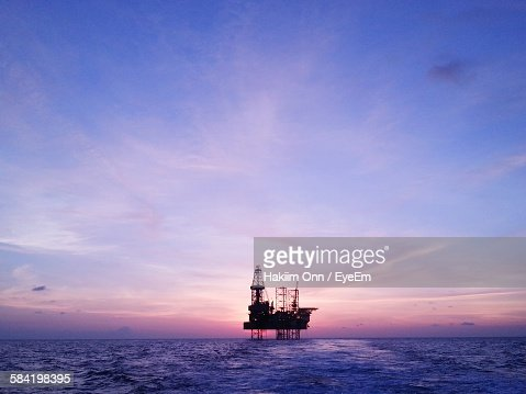 Silhouette Oil Rig In Sea Against Sky During Sunset