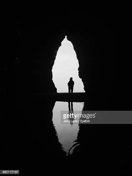 Silhouette On Boat In Cave Entrance