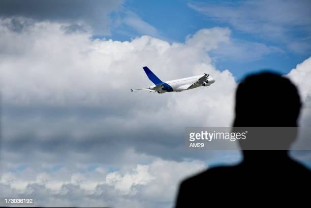 Silhouette on man watching plane take off