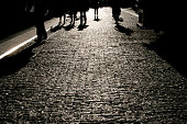 Shadows of people walking in a street of the city