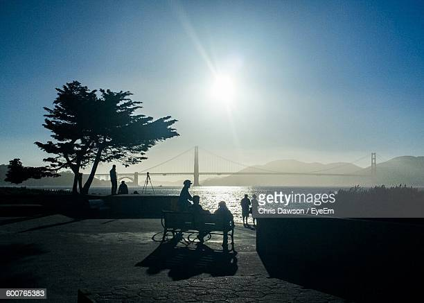 Silhouette People At Promenade By Bay With Golden Gate Bridge Against Sky