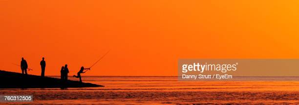 Silhouette People Fishing On Shore At Beach Against Sky During Sunset